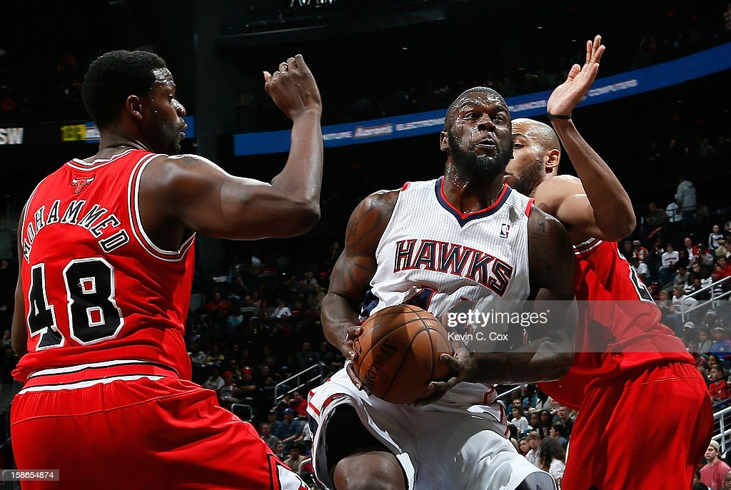 Ivan Johnson #44 of the Atlanta Hawks drives against Nazr Mohammed #48 and Taj Gibson #22 of the Chicago Bulls at Philips Arena on December 22, 2012 in Atlanta, Georgia.