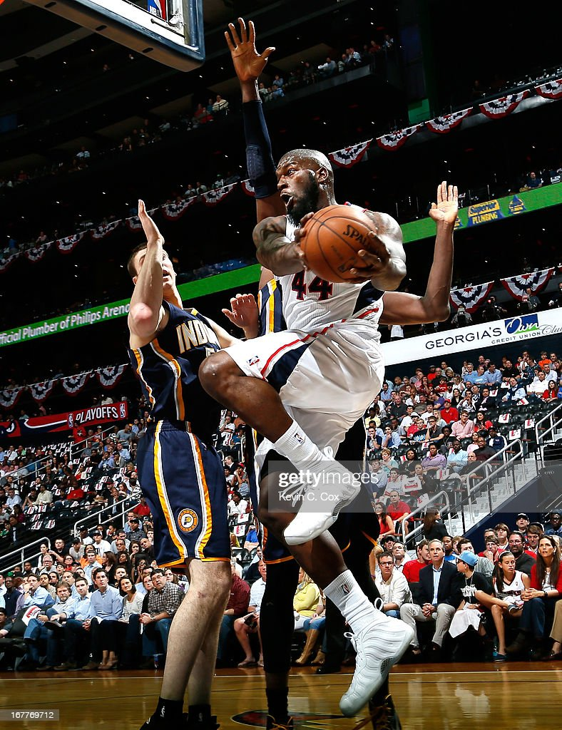 Ivan Johnson of the Atlanta Hawks drives against Tyler Hansbrough and Roy Hibbert of the Indiana Pacers during Game Four of the Eastern Conference...
