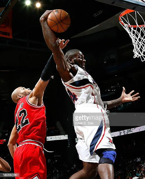 Ivan Johnson of the Atlanta Hawks grabs a rebound against Taj Gibson of the Chicago Bulls at Philips Arena on February 2 2013 in Atlanta Georgia NOTE...