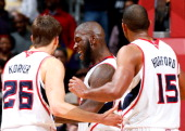 Ivan Johnson of the Atlanta Hawks reacts with Kyle Korver and Al Horford after a basket against the Los Angeles Lakers at Philips Arena on March 13...