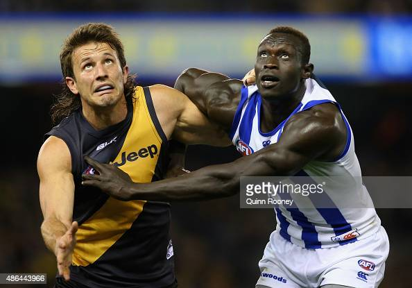 Ivan Maric of the Tigers and Majak Daw of the Kangaroos compete in the ruck during the round 23 AFL match between the Richmond Tigers and the North...