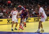 Ivan Nikcevic of Serbia scores a goal against Jakov Gojun of Croatia during the Men's European Handball Championship second semi final match between...