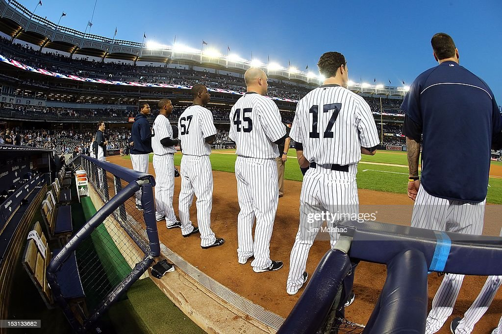 Ivan Nova #47, Eduardo Nunez #26, Melky Mesa #67, Casey McGehee #45, Jayson Nix #17 and Joba Chamberlain #62 of the New York Yankees stand for the national anthem before playing against the Oakland Athletics at Yankee Stadium on September 21, 2012 in the Bronx borough of New York City. The Yankees defeated the A's 2-1.