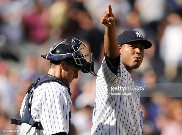 Ivan Nova of the New York Yankees celebrates a win over the San Francisco Giants with Chris Stewart during interleague play on September 21 2013 at...