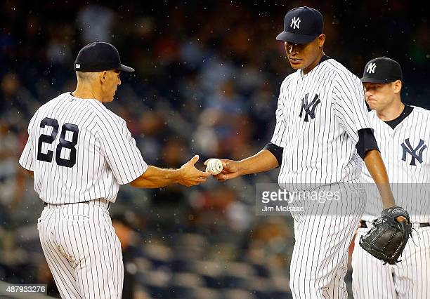 Ivan Nova of the New York Yankees hands the ball to manager Joe Girardi as he leaves a game in the second inning against the Toronto Blue Jays at...