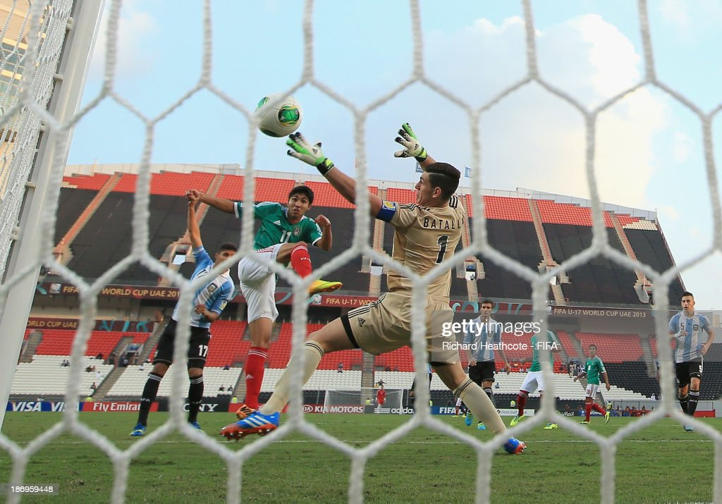 Ivan Ochoa of Mexico shoots past Augusto Batalla of Argentina to score the opening goal during the FIFA U-17 World Cup UAE 2013 Semi Final match between Argentina and Mexico at the Mohamed Bin Zayed Stadium on November 5, 2013 in Abu Dhabi, United Arab Emirates.