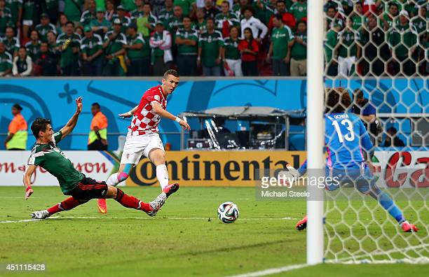 Ivan Perisic of Croatia shoots and scores his team's first goal past Guillermo Ochoa of Mexico during the 2014 FIFA World Cup Brazil Group A match...