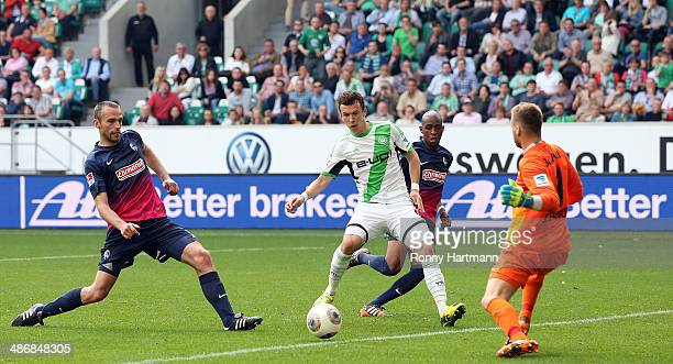 Ivan Perisic of Wolfsburg scores his team's second goal against goalkeeper Oliver Baumann of Freiburg during the Bundesliga match between VfL...