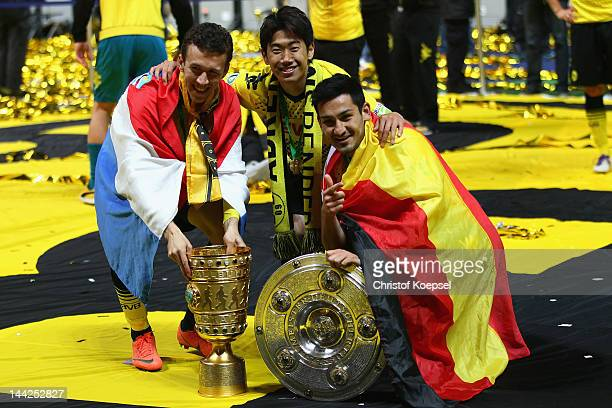 Ivan Perisic Shinji Kagawa and Ilkay Guendogan of Dortmund pose with the trophies after winning the DFB Cup final match between Borussia Dortmund and...