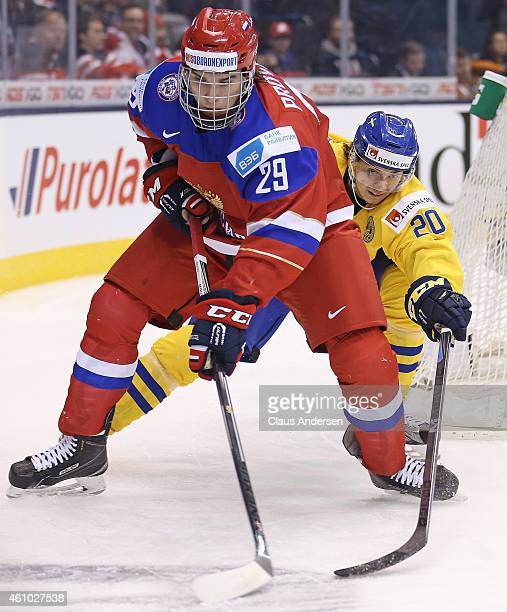 Ivan Provorov of Team Russia protects the puck against Adam Brodecki of Team Sweden during a semifinal game in the 2015 IIHF World Junior Hockey...