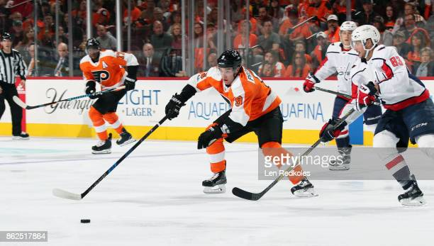 Ivan Provorov of the Philadelphia Flyers battles for the loose puck against Jay Beagle of the Washington Capitals on October 14 2017 at the Wells...