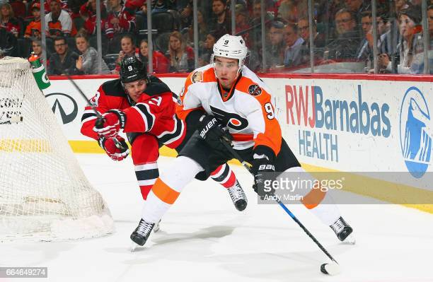 Ivan Provorov of the Philadelphia Flyers plays the puck while being pursued by Taylor Hall of the New Jersey Devils during the game at Prudential...