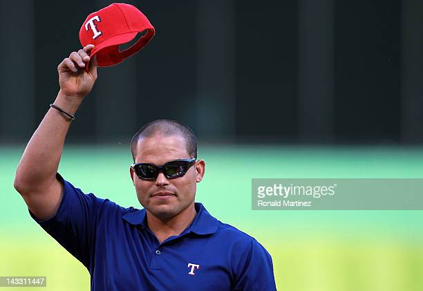 Ivan 'Pudge' Rodriguez tips his Texas Rangers hat during a retirement ceremony before a game against the New York Yankees at Rangers Ballpark in...