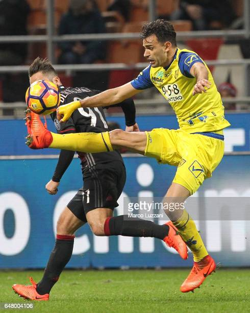 Ivan Radovanovic of AC Chievo Verona is challenged by Andrea Bertolacci of AC Milan during the Serie A match between AC Milan and AC ChievoVerona at...