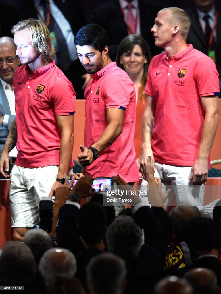 Ivan Rakitic, Luis Suarez and Jeremy Mathieu of FC Barcelona acknowledge the FC Barcelona supporters during the new FC Barcelona players presentation as part of the FC Barcelona Fans Association's conference at Palau de Congressos de Catalunya on August 18, 2014 in Barcelona, Spain.
