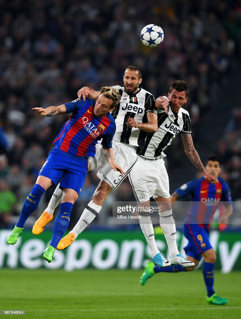 Ivan Rakitic of Barcelona jumps for the ball with Giorgio Chiellini and Mario Mandzukic of Juventus during the UEFA Champions League Quarter Final first leg match between Juventus and FC Barcelona at Juventus Stadium on April 11, 2017 in Turin, Italy.