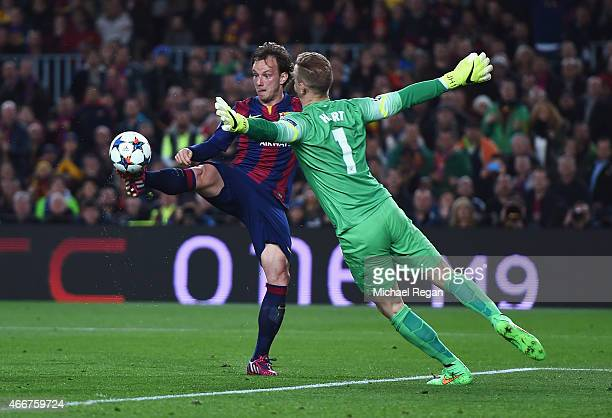 Ivan Rakitic of Barcelona lifts the ball over Joe Hart of Manchester City to score the opening goal during the UEFA Champions League Round of 16...