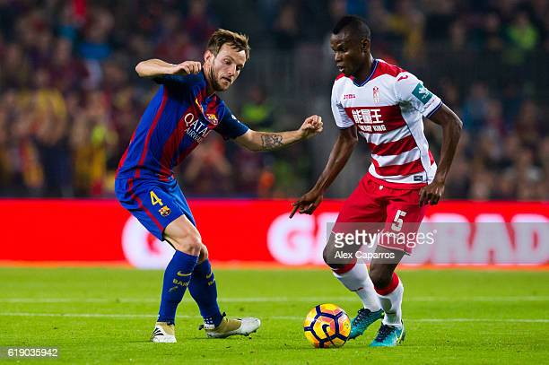Ivan Rakitic of FC Barcelona and Uche Henry Agbo of Granada CF compete for the ball during the La Liga match between FC Barcelona and Granada CF at...