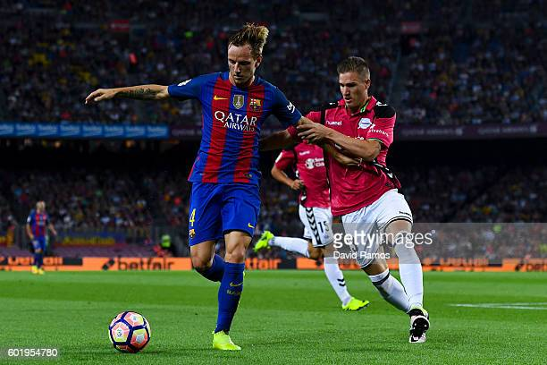 Ivan Rakitic of FC Barcelona competes for the ball with Raul Garcia of Deportivo Alaves during the La Liga match between FC Barcelona and Deportivo...