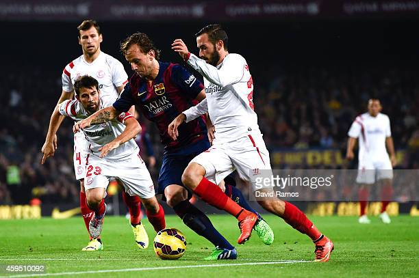 Ivan Rakitic of FC Barcelona competes for the ball with Sevilla FC players during the La Liga mach between FC Barcelona and Sevilla FC at Camp Nou on...
