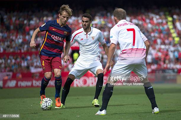 Ivan Rakitic of FC Barcelona competes for the ball with Vicente Iborra and his teammate Michael KrohnDehli during the La Liga match between Sevilla...
