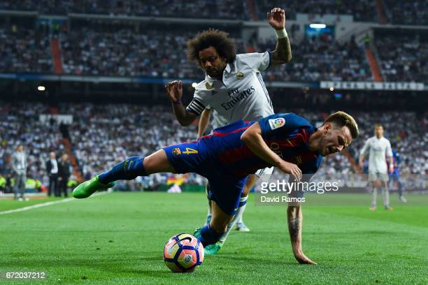 Ivan Rakitic of FC Barcelona is brought down by Marcelo Vieira of Real Madrid CF during the La Liga match between Real Madrid CF and FC Barcelona at...