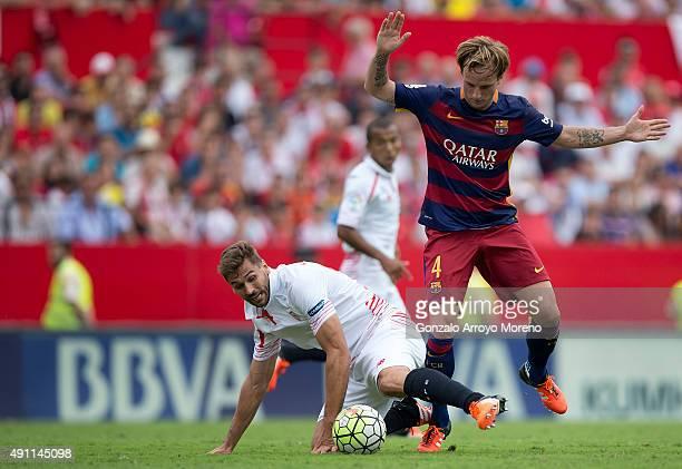 Ivan Rakitic of FC Barcelona tackles Fernando Llorente of Sevilla FC during the La Liga match between Sevilla FC and FC Barcelona at Estadio Ramon...