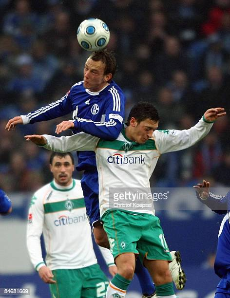 Ivan Rakitic of Schalke and Mesut Oezil of Bremen go up for a header during the Bundesliga match between FC Schalke 04 and Werder Bremen at the...