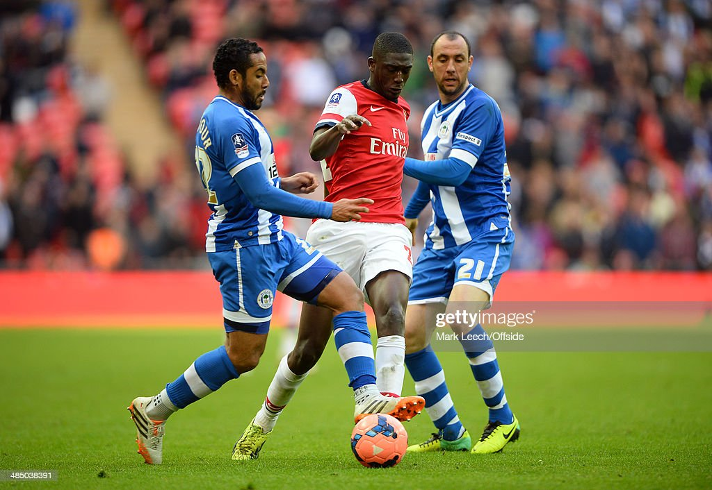 Ivan Ramis and Jean Beausejour of Wigan Athletic of Wigan Athletic in action with Yaya Sanogo of Arsenal during the FA Cup SemiFinal match between...