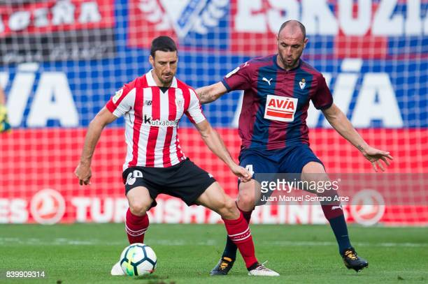 Ivan Ramis of SD Eibar duels for the ball with Aritz Aduriz of Athletic Club during the La Liga match between Eibar and Athletic Club at Estadio...