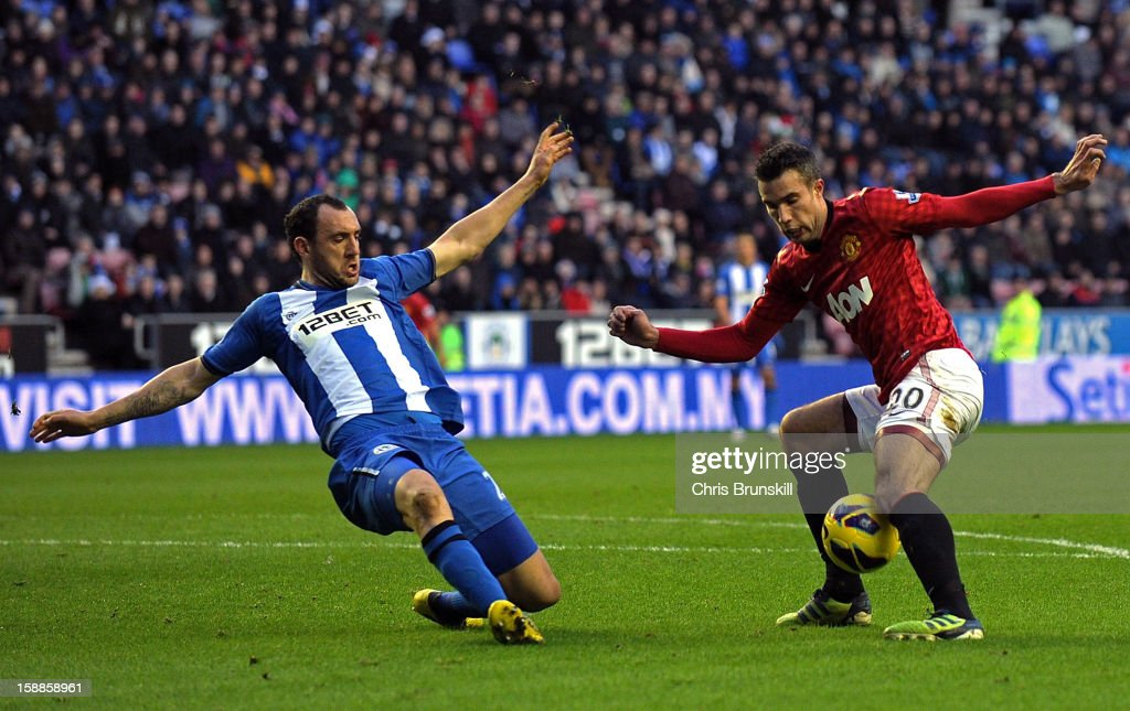 Ivan Ramis of Wigan Athletic in action with Robin Van Persie of Manchester United during the Barclays Premier League match between Wigan Athletic and...