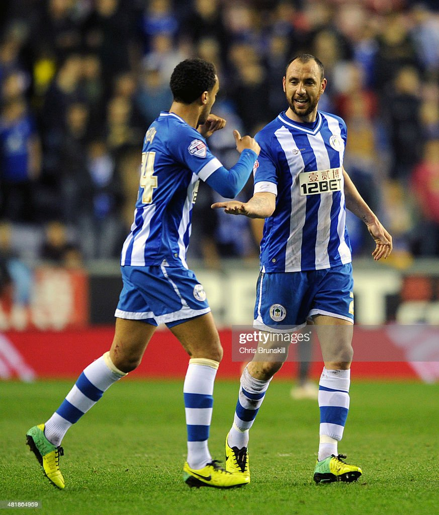 Ivan Ramis (R) of Wigan Athletic is congratulated by team-mate James Perch after scoring the opening goal during the Sky Bet Championship match between Wigan Athletic and Leicester City at DW Stadium on April 01, 2014 in Wigan, England.