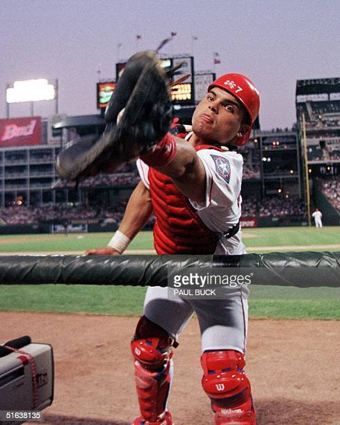 Ivan Rodriguez of the Texas Rangers reaches in to the photographer's well to catch a pop foul against the Los Angeles Dodgers 01 July at The Ballpark...