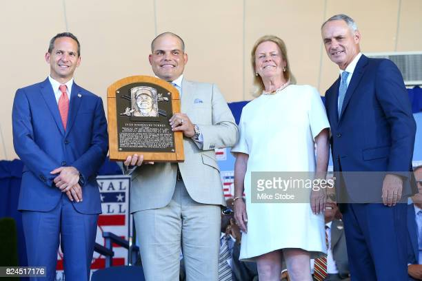 Ivan Rodriguez poses for a photograph as he is presented his plaque with Hall of Fame President Jeff Idelson Hall of Fame chairman of the board Jane...