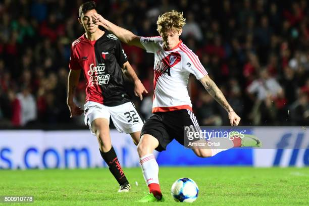 Ivan Rossi of River Plate kicks the ball while is followed by Tomas Sandoval of Colon during a match between Colon and River Plate as part of Torneo...