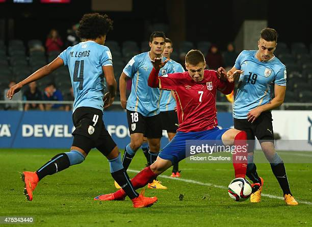 Ivan Saponjic of Serbia is challenged by Mauricio Lemos and Erick Cabaco of Uruguay during the FIFA U20 World Cup New Zealand 2015 Group D match...