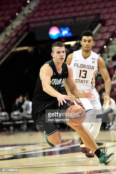 Ivan Tomic guard Thomas University Night Hawks runs ahead of Anthony Polite guard Florida State University Seminoles in an exhibition basketball game...