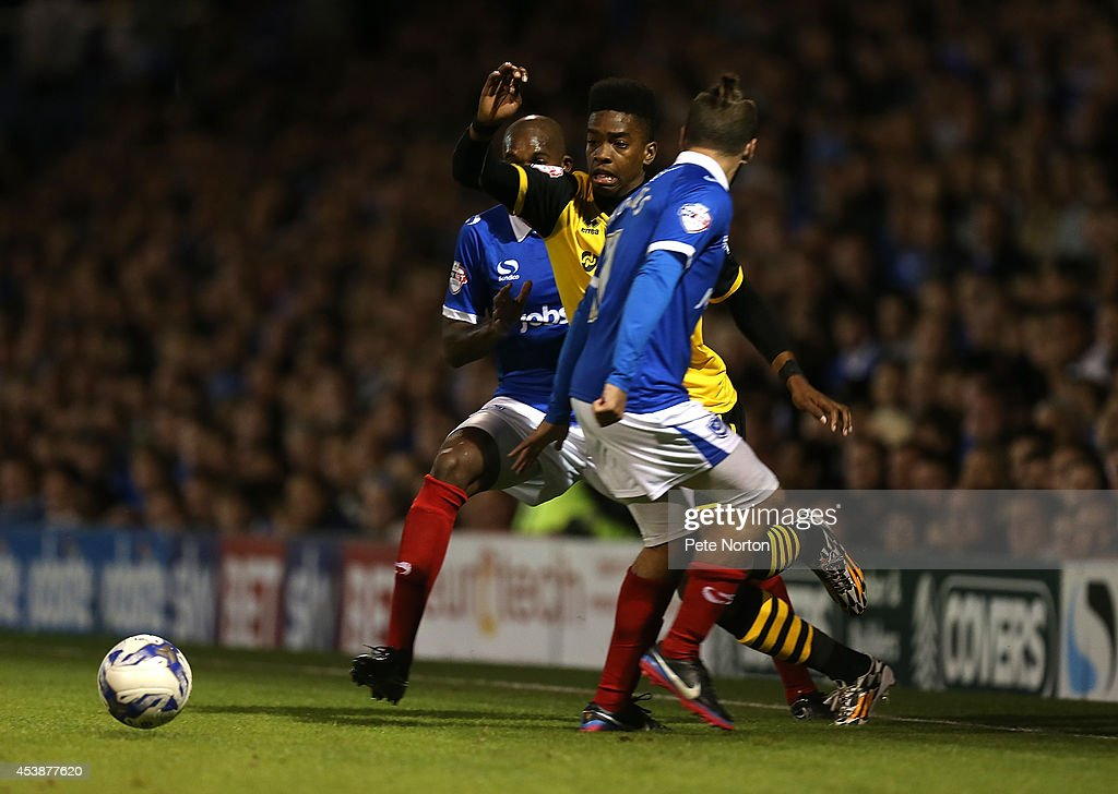 Ivan Toney of Northampton Town attempts to move with the ball between Ricky Holmes and Nigel Atangana of Portsmouth to head the ball during the Sky Bet League Two match between Portsmouth and Northampton Town at Fratton Park on August 19, 2014 in Portsmouth, England.