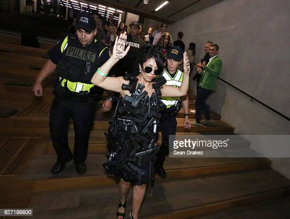 Ivana Zambrana of Spain is escorted away from guests by Miami Police officers as she performs 'Fear Kills' produced by Isagus Extroversions at Perez...
