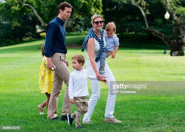 Ivanka Trump daughter of US President Donald Trump carries her son Theodore as she holds hands with son Joseph alongside her husband Jared Kushner...
