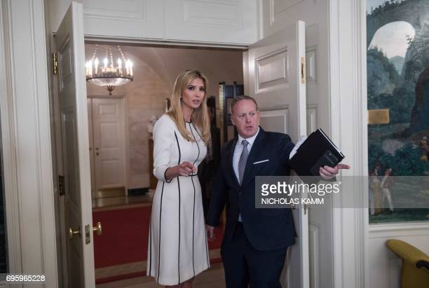 Ivanka Trump daughter of US President Donald Trump speaks with White House spokesman Sean Spicer after her father delivered a statement in the...