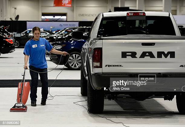 Ivena Strauser listens to music while vacuuming carpet next to a 2016 Dodge Ram 1500 Rebel crew cab 4x4 in preparation for the Denver Auto Show at...