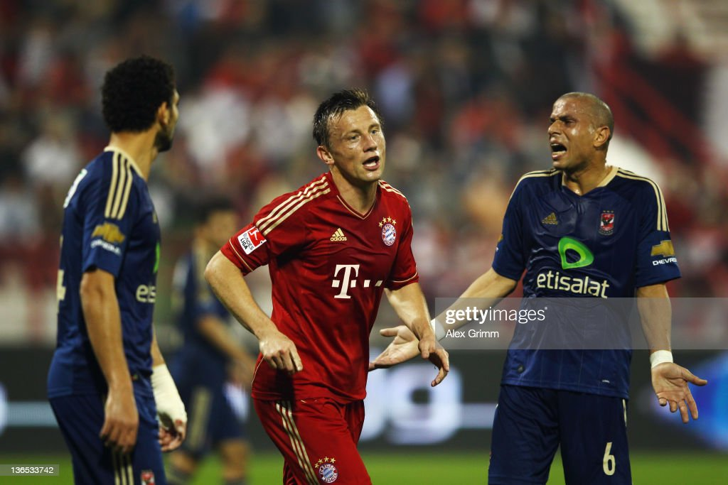 Ivica Olic of Muenchen celebrates his team's first goal as Hossam Ghaly and Wael Gomaa of AlAhly react during the international friendly match...