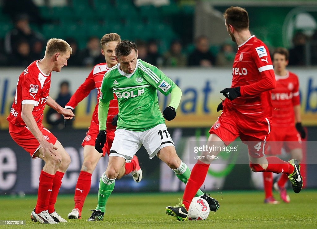 Ivica Olic (C) of Wolfsburg and Axel Bellinghausen (L) and Johannes van den Bergh (2nd L) of Duesseldorf compete for the ball during the Bundesliga match between VfL Wolfsburg and Fortuna Duesseldorf 1895 at Volkswagen Arena on March 15, 2013 in Wolfsburg, Germany.