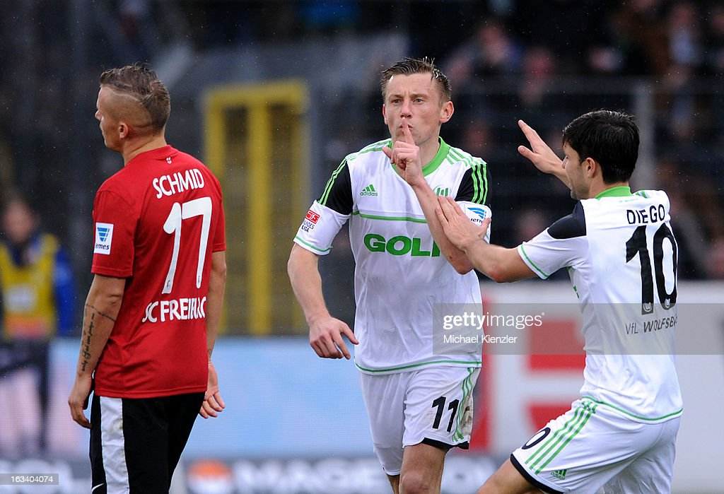 Ivica Olic (C) of Wolfsburg celebrates his 4:1 with Diego during the Bundesliga match between SC Freiburg and VfL Wolfsburg at MAGE SOLAR Stadium on March 9, 2013 in Freiburg, Germany. On left side Jonathan Schmid of Freiburg.