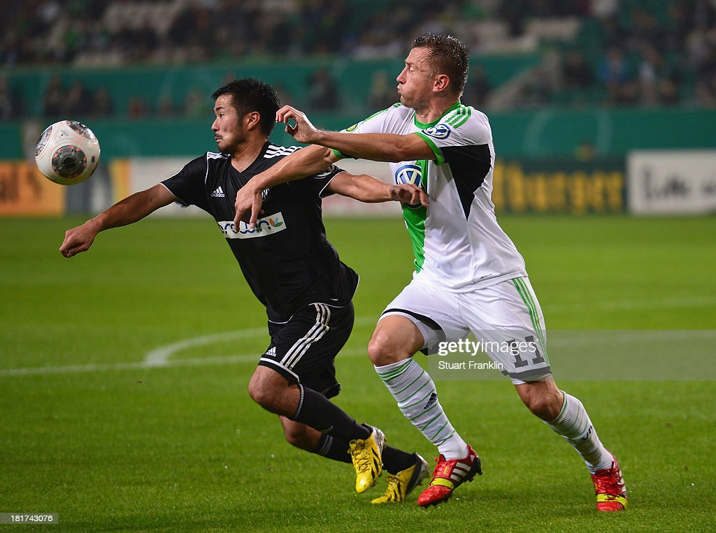 <a gi-track='captionPersonalityLinkClicked' href=/galleries/search?phrase=Ivica+Olic&family=editorial&specificpeople=547277 ng-click='$event.stopPropagation()'>Ivica Olic</a> of Wolfsburg is challenged by Takuma Abe of Aalen during the second round DFB cup match between VfL Wolfsburg and Vfr Aalen at Volkswagen Arena on September 24, 2013 in Wolfsburg, Germany.