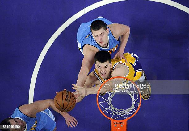 Ivica Zubac of the Los Angeles Lakers battle for a rebound against Nikola Jokic and Danilo Gallinari of the Denver Nuggets during the first half of...