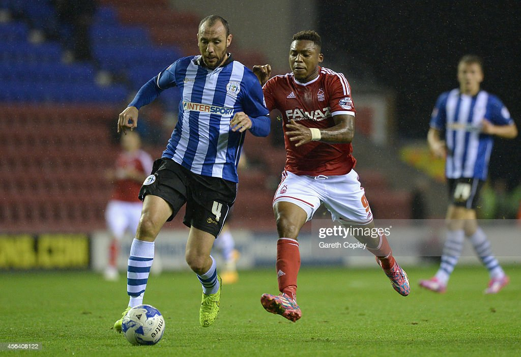 Iván Ramis of Wigan Athletic is tackled by Britt Assombalonga of Nottingham Forest during the Sky Bet Championship between Wigan Athletic and...