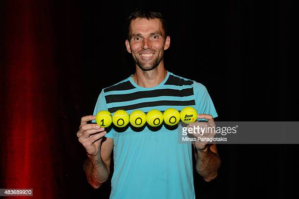 Ivo Karlovic of Croatia holds up a set of tennis balls with the number ten thousand becoming the second player in history to reach 10000 aces during...