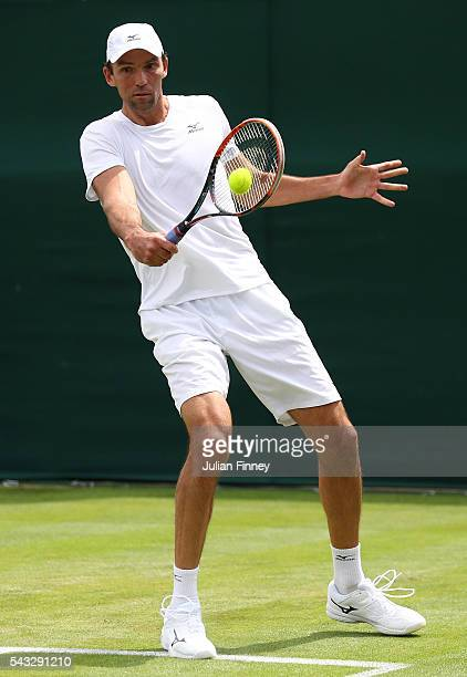 Ivo Karlovic plays a backhand shot during the Men's Singles first round match against Borna Coric of Croatia on day one of the Wimbledon Lawn Tennis...
